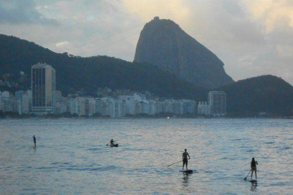 Varios surfers con el Pan de Azúcar al atardecer stand up paddle rio de janeiro